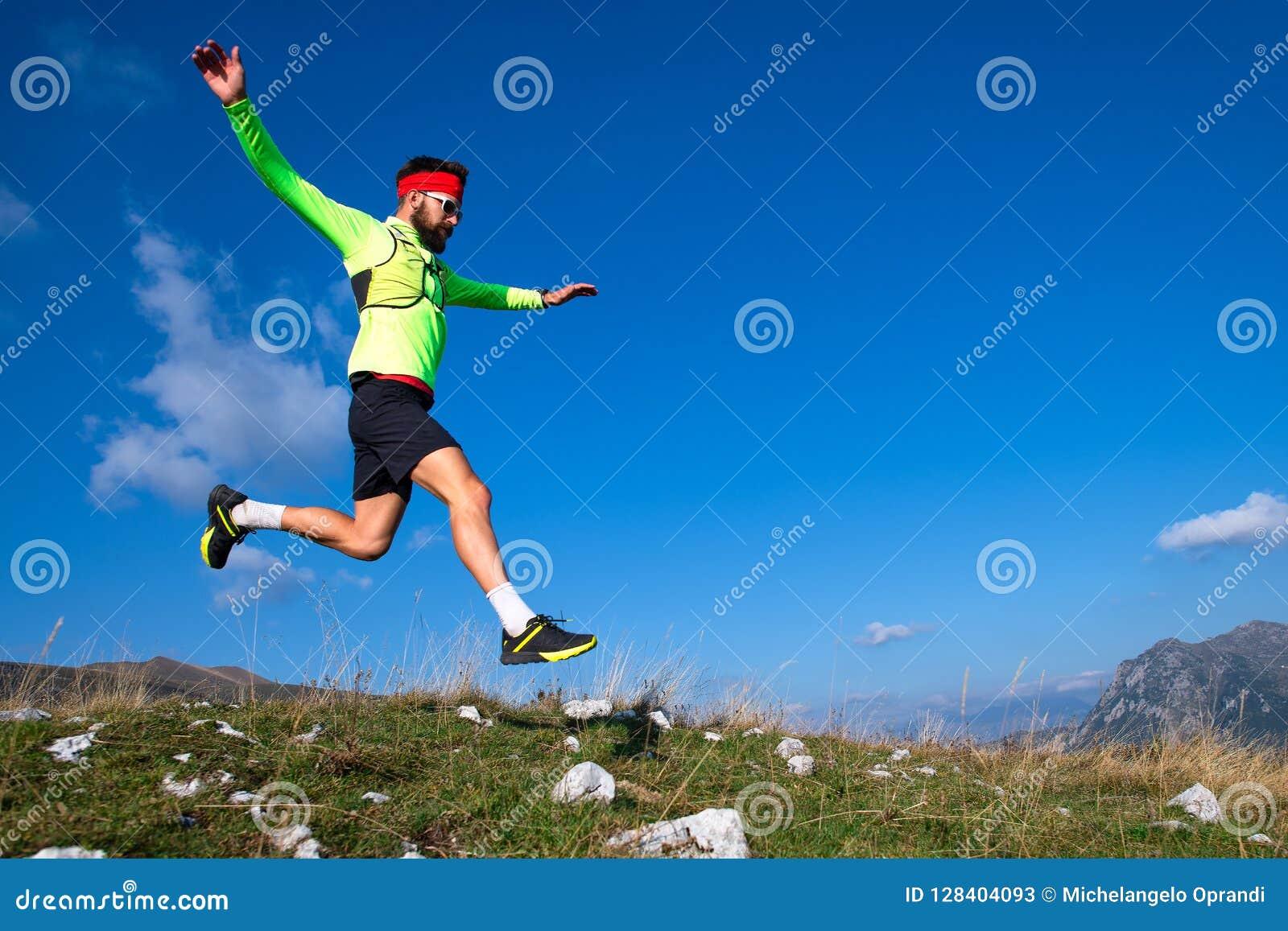 Skyrunner durante um salto em declive em prados da montanha
