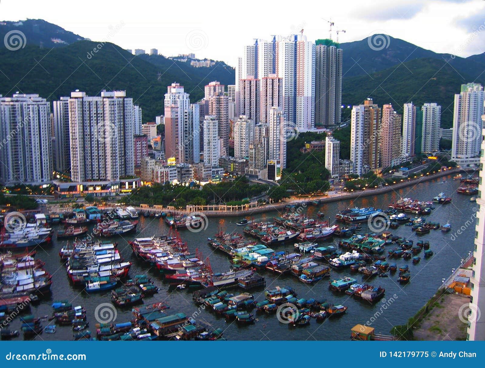 Skyview das construções altas e dos barcos de pesca pequenos em Hong Kong