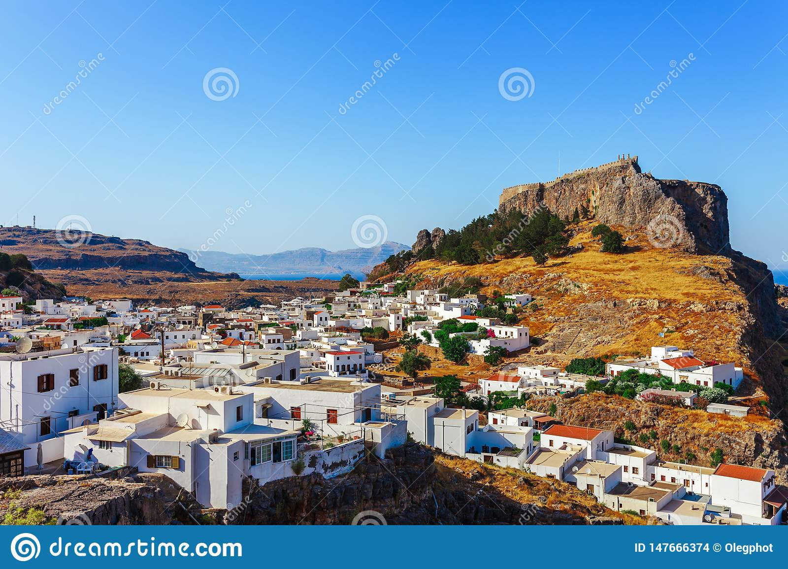 Skyview landscape photo Lindos town and ancient castle on Rhodes island, Dodecanese, Greece. Panorama with mountains and sea.