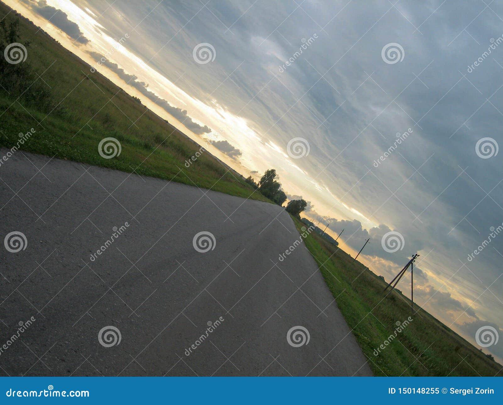 Slät rak asfaltväg i bygden under himlen med moln på solnedgången