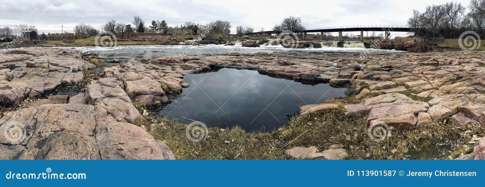 Slå samman reflexionen av himlen med den stora Sioux River i Sioux Falls South Dakota med sikter av djurliv, fördärvar, parkerar