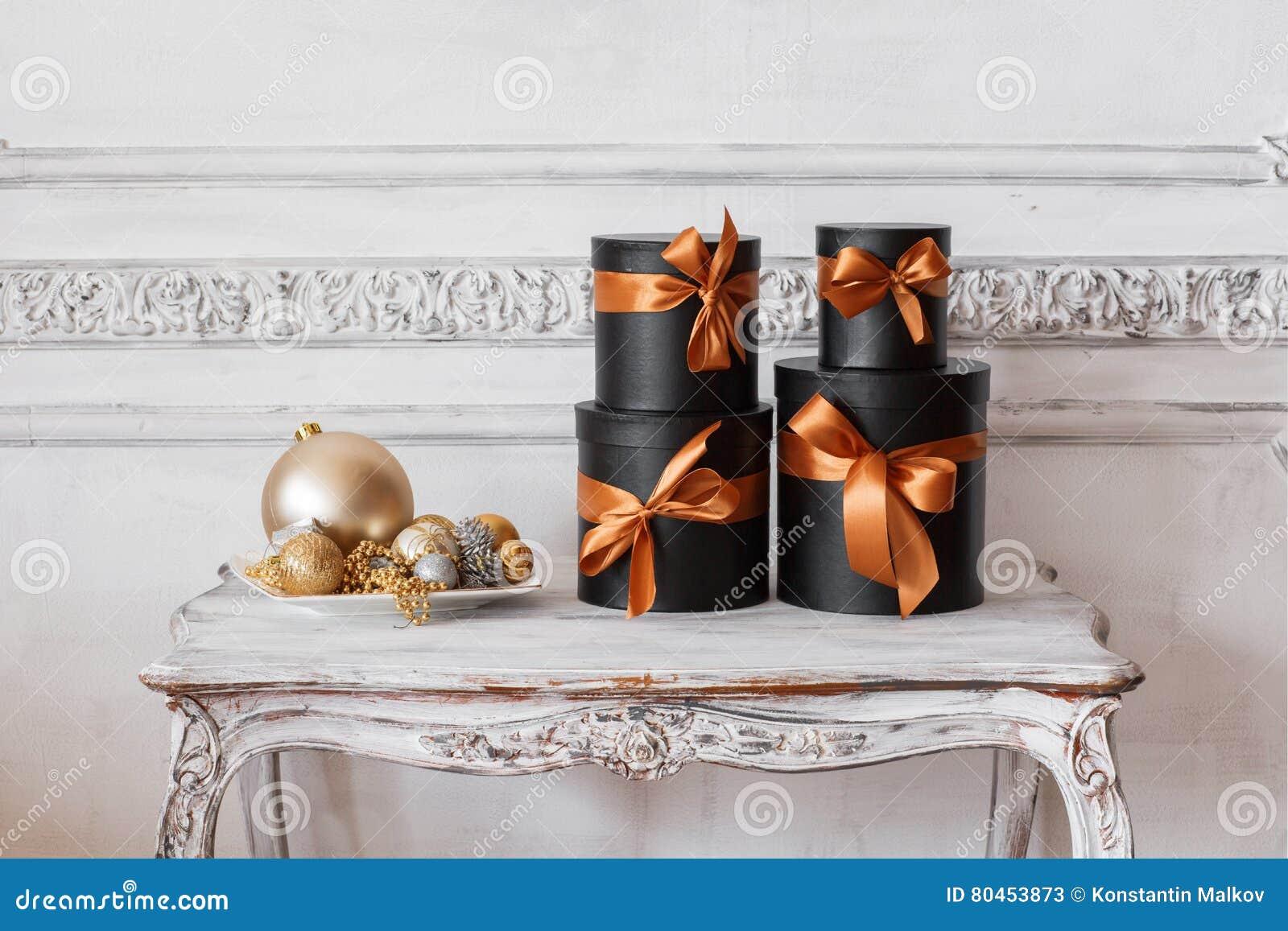 Slågna in svarta askar för gåva med band, som julklappar på en lyxig vit vägg för tabell planlägger basreliefstuckaturen