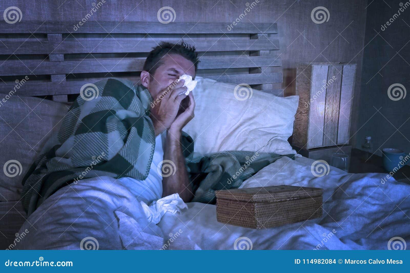 Slösat sjukt hemmastatt frysa för man i säng som täckas med filten som sniffar att nysa och att blåsa näslidandegrippe som känner