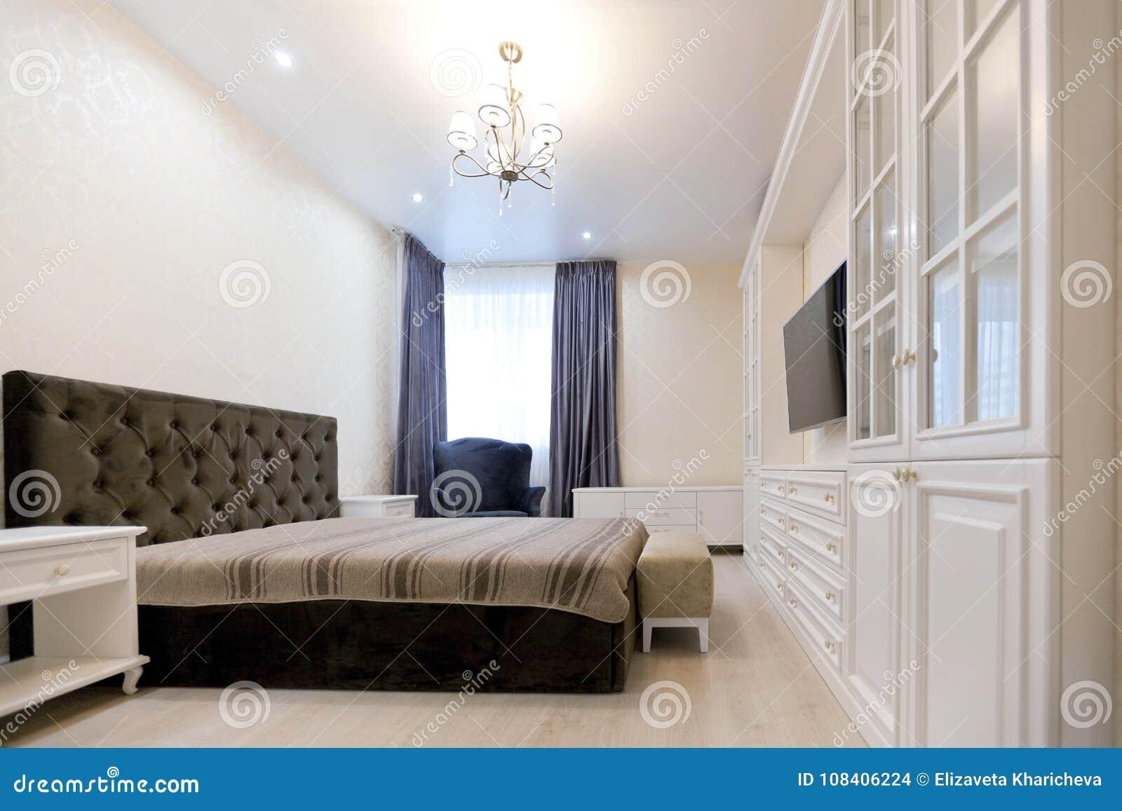 Slaapkamer in lichte kleuren met donker bed en blauwe gordijnen