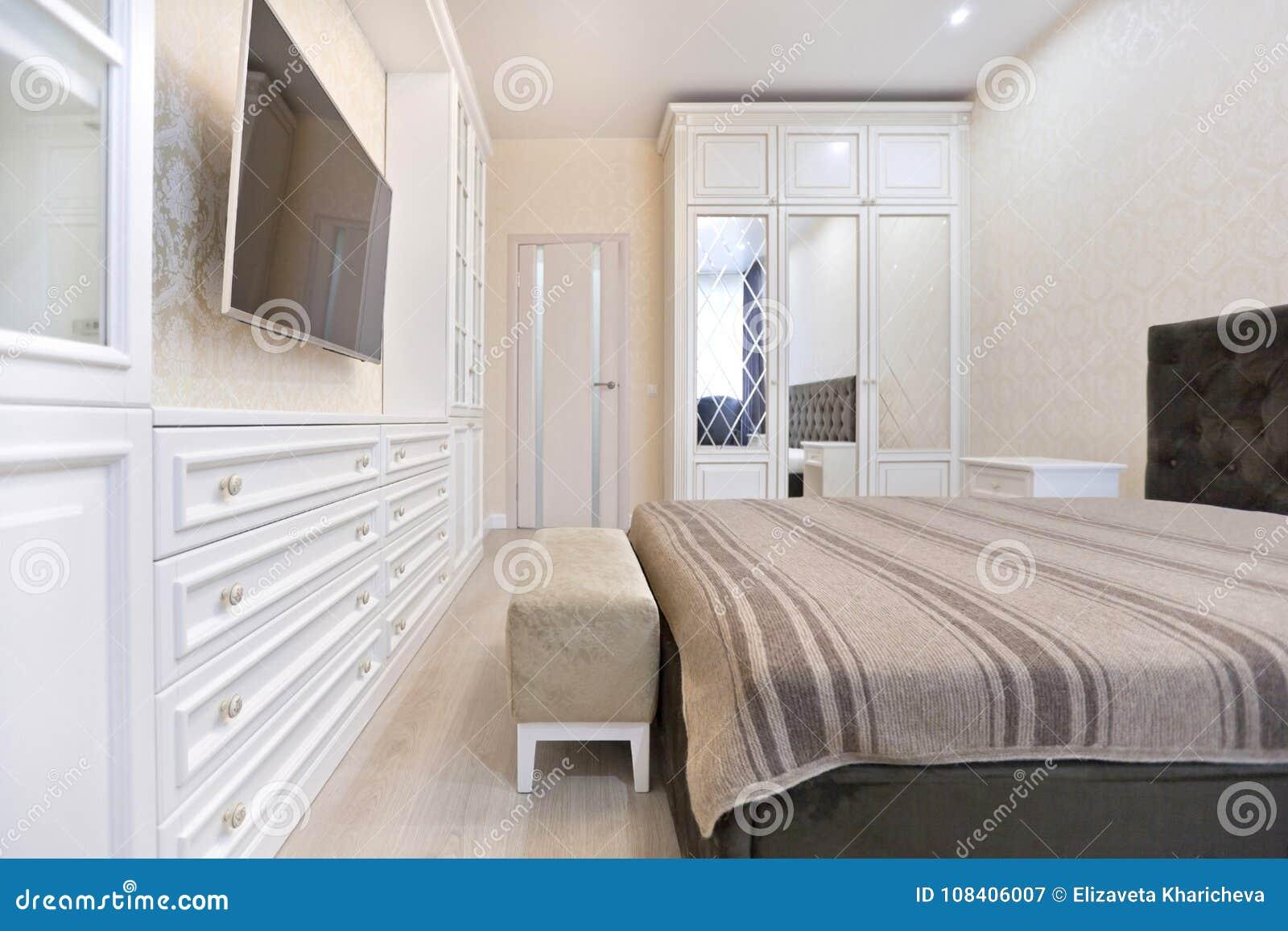Kleuren Voor Slaapkamer : Slaapkamer in lichte kleuren met donker bed en tv meubilair stock