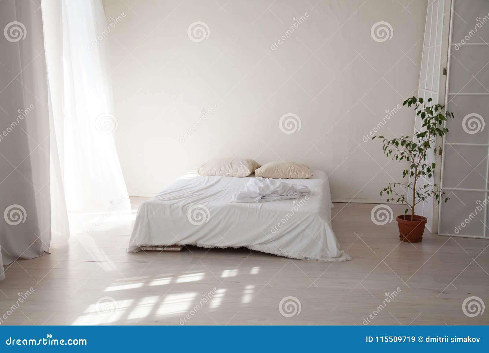 Slaapkamer Groen Wit : Slaapkamer met een wit bed en een groene installatie stock