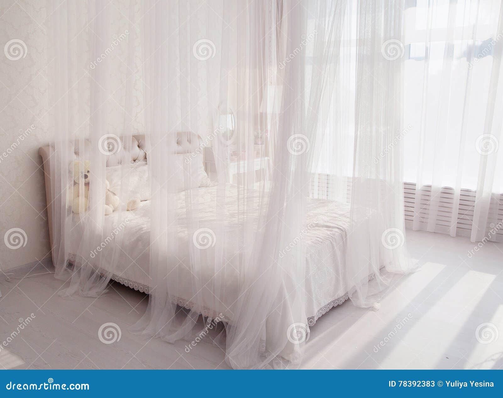 Slaapkamer met een wit bed grote spiegel dichtbij het