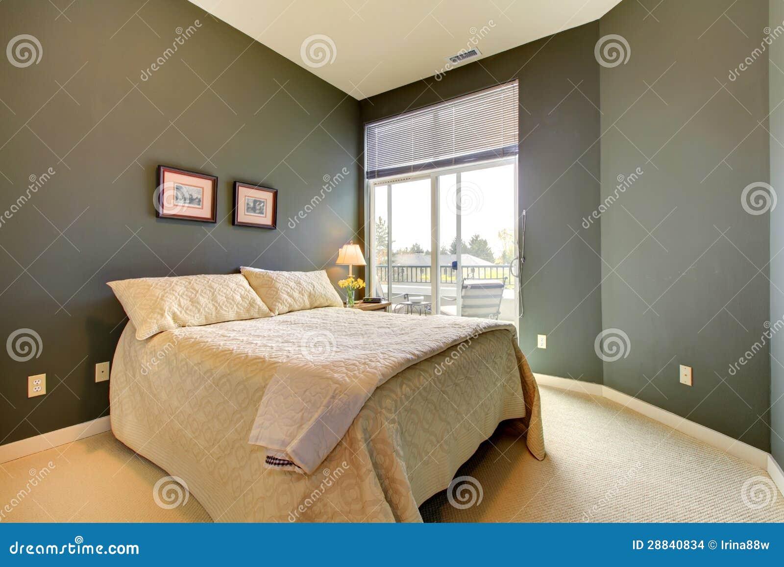 Slaapkamer met grijze groene muren en wit beddegoed. De deur van het ...