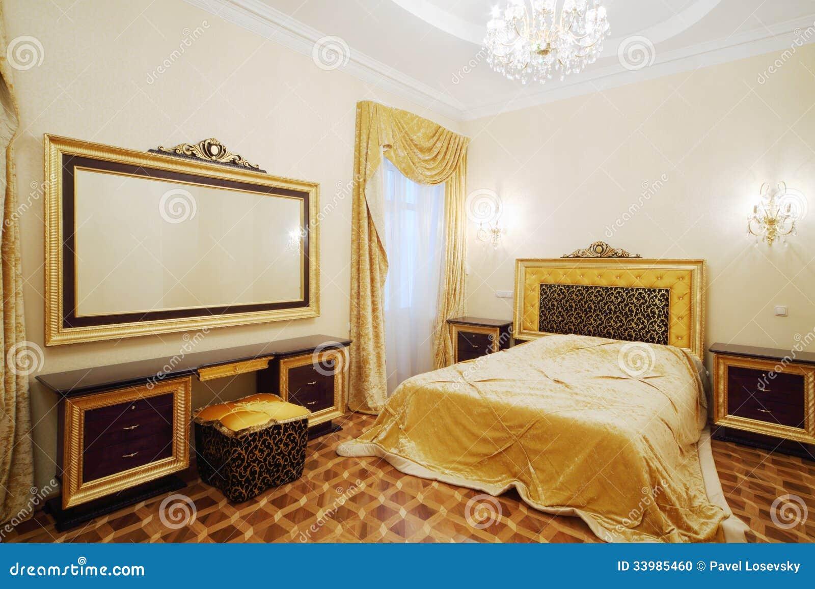 Slaapkamer met mooi bed bedlijsten en grote spiegel stock foto