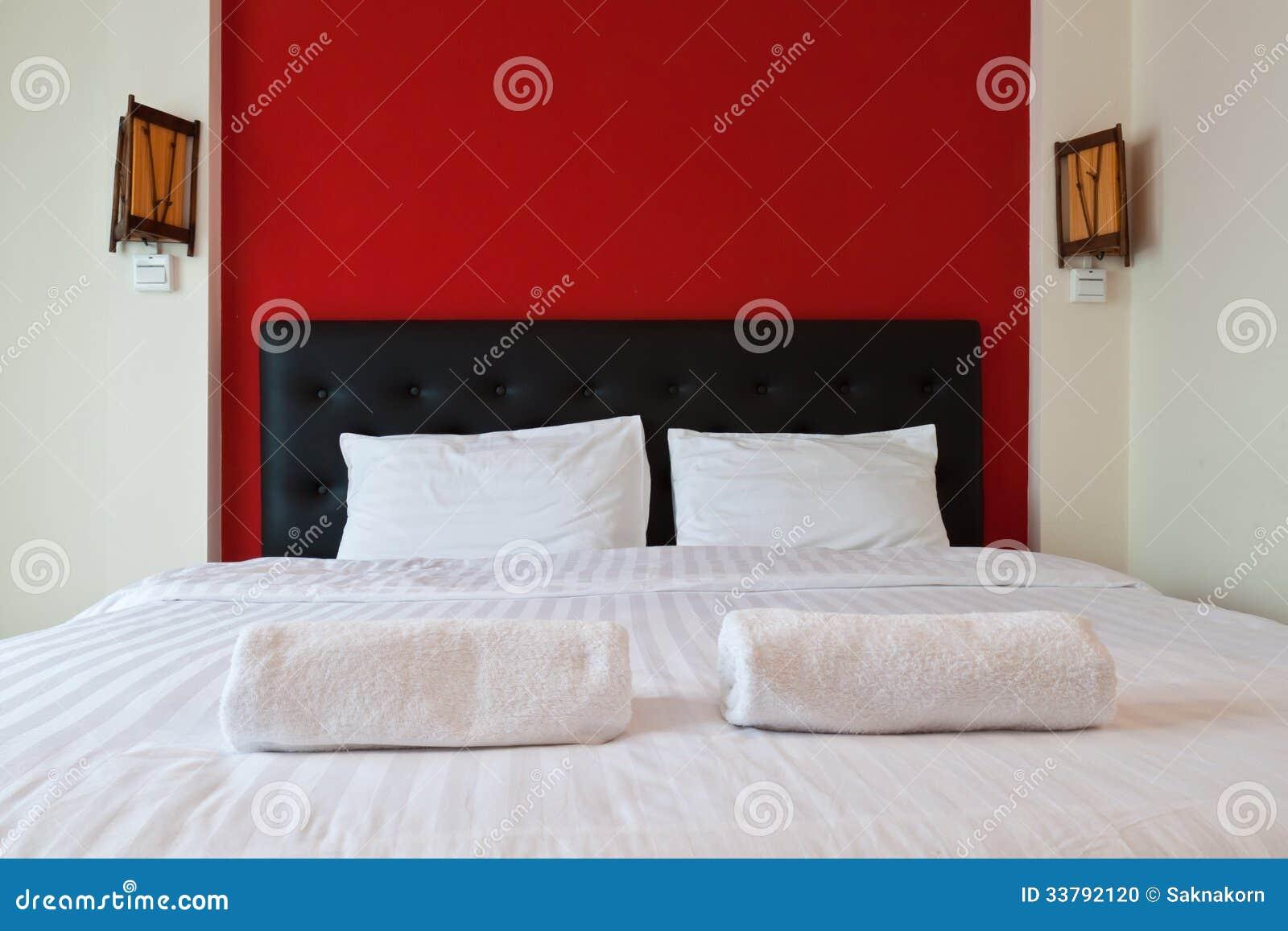 Slaapkamer met rode muur, handdoek op het bed. stock foto ...