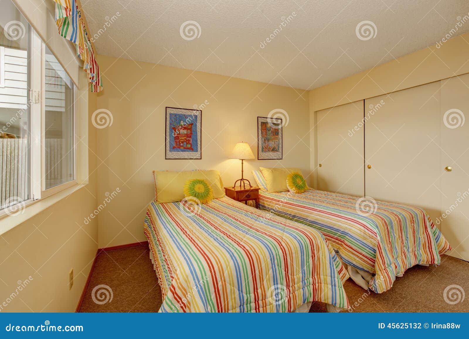 Slaapkamer met twee eenpersoonsbedden in vrolijk beddegoed stock ...
