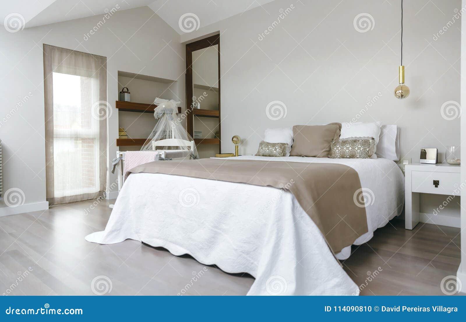 Slaapkamer met tweepersoonsbed en wieg stock foto afbeelding