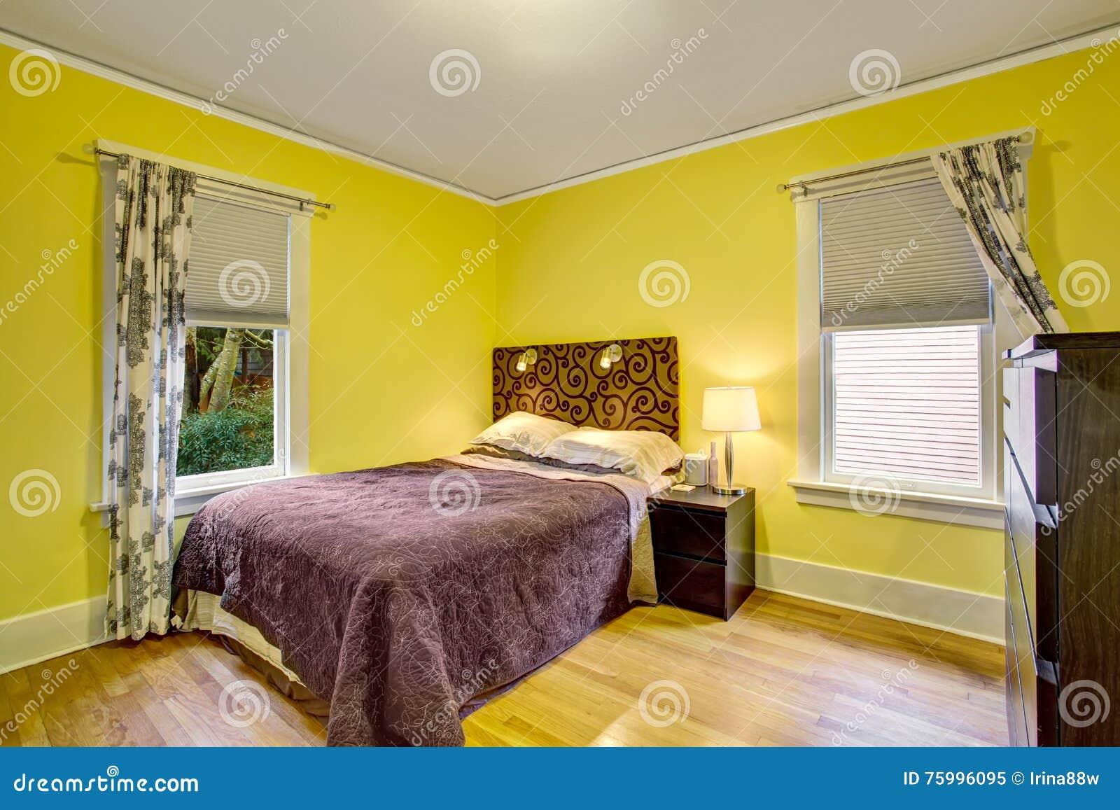 Gele Muur Slaapkamer : Slaapkamerbinnenland met gele muren en donkerbruin meubilair stock