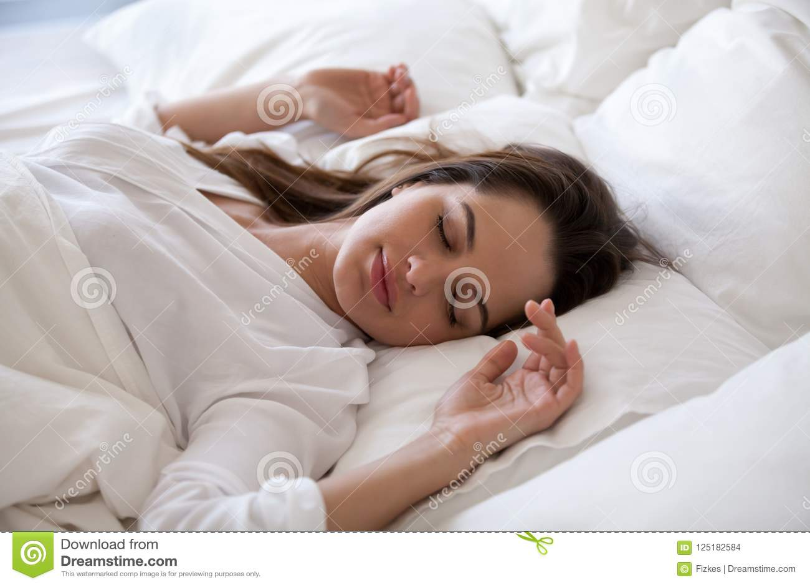 Slaapvrouw die van rust in comfortabel bed in de ochtend genieten