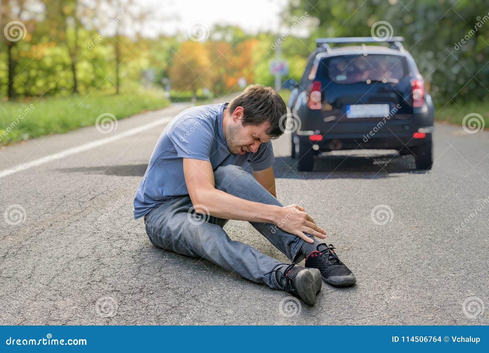 Slag- och körningsbegrepp Sårad man på vägen framme av en bil