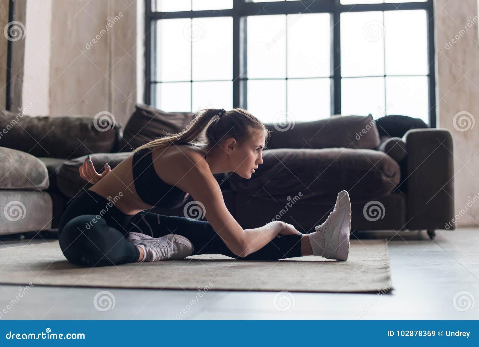 Slank idrottskvinna i sportswear som värmer muskler upp för genomkörare som gör sträcka övningssammanträde på golv hemma