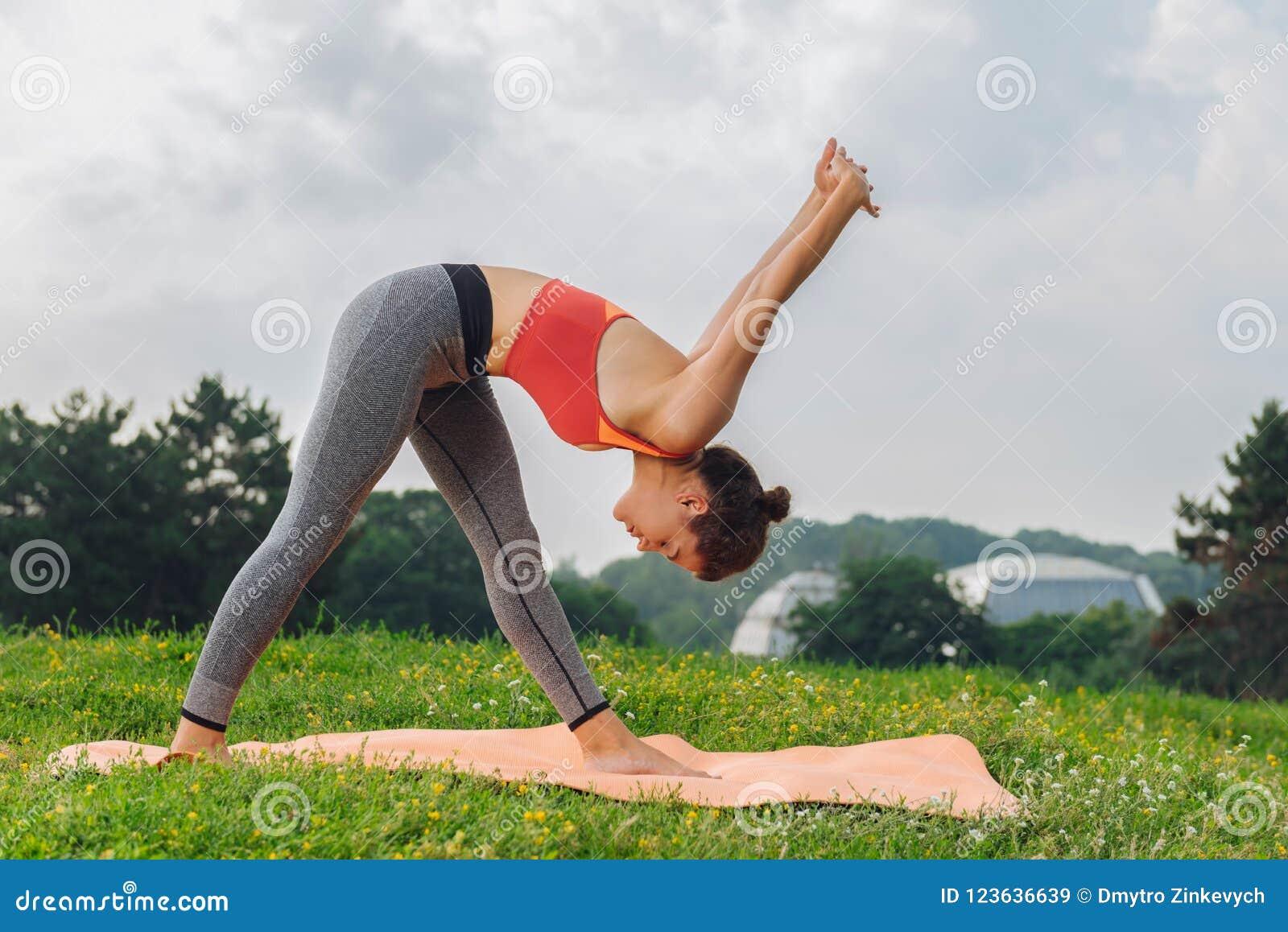 Slank idrottskvinna som in går för yogaanseendet på grönt gräs