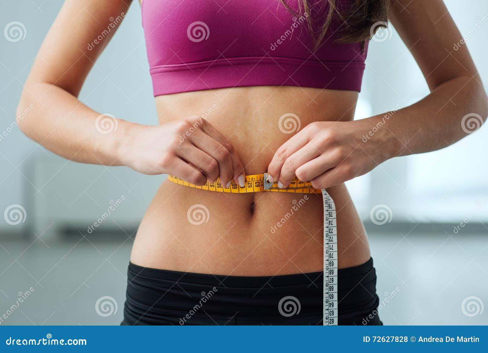 19d91ae3 Banta den unga kvinnan som mäter hennes tunna midja med en måttband, slut  upp