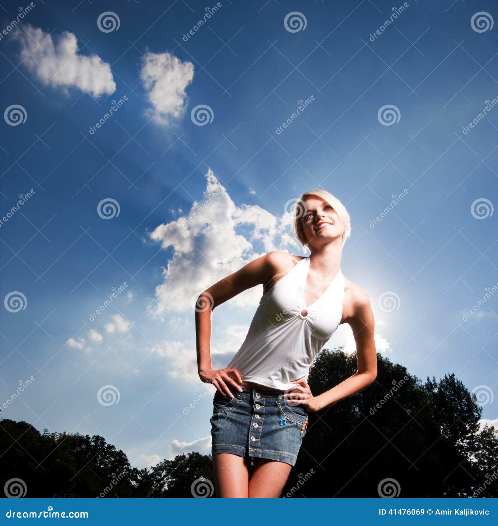 Slank ung kvinna med händer på midjan