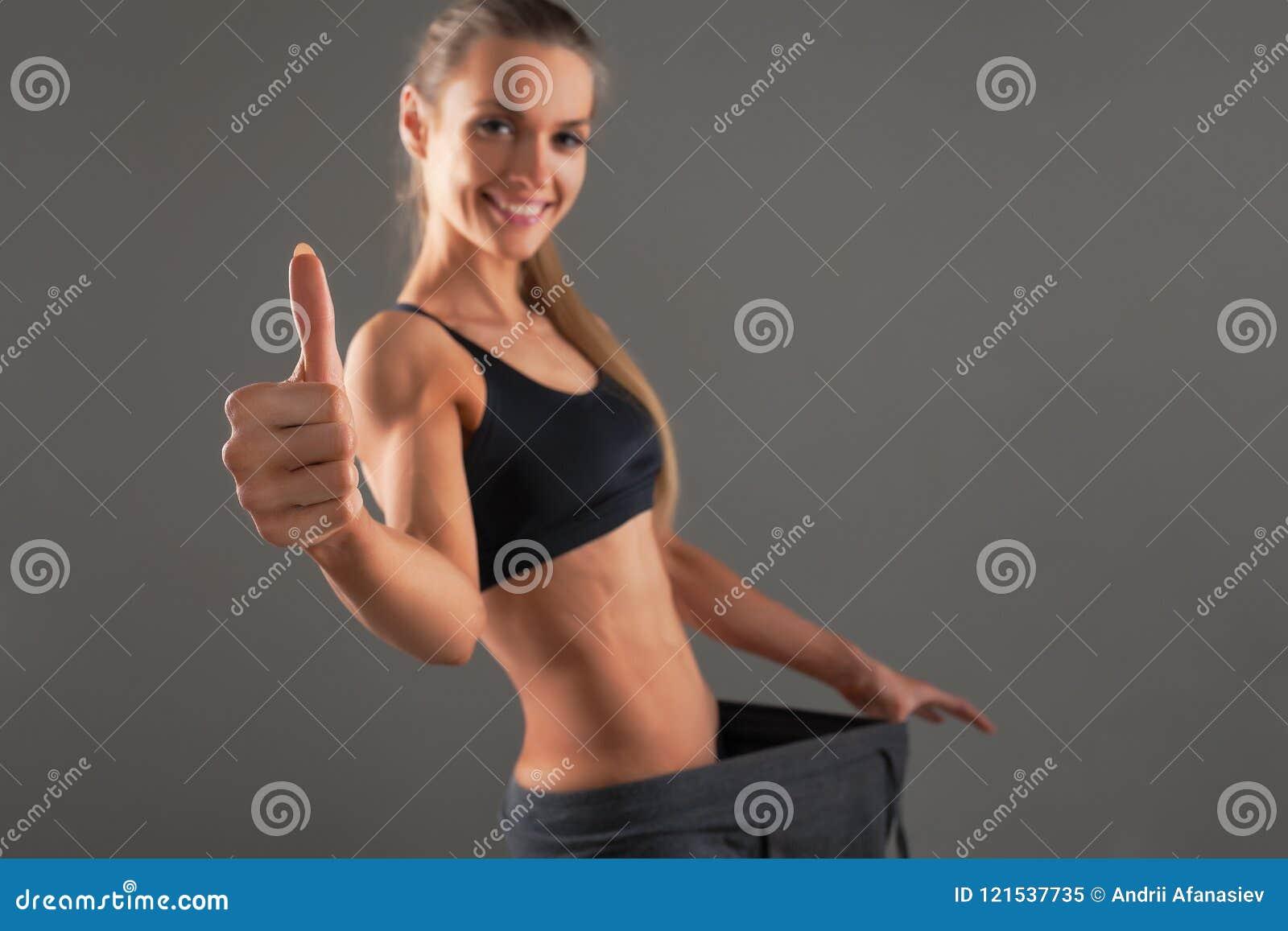 Slank ung kvinna som bär gamla stora flåsanden som visar det lyckade resultatet av en banta - viktförlust som bantar begrepp Grå