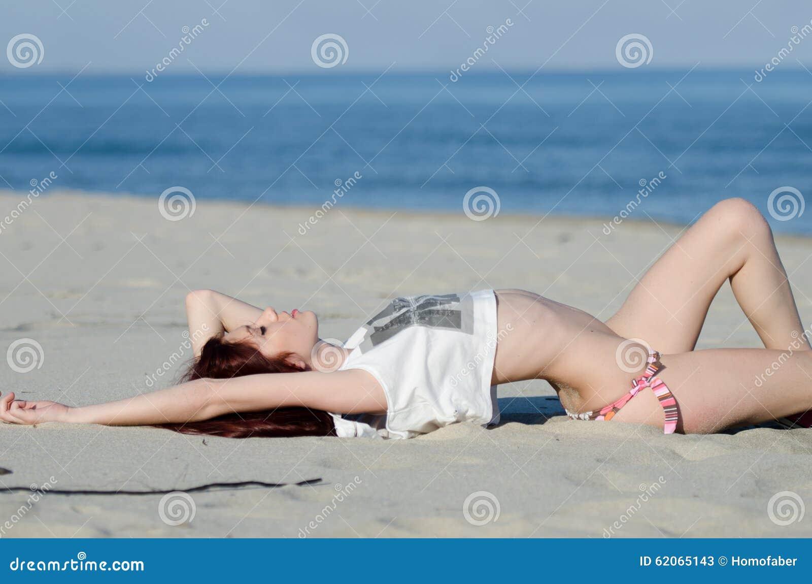 Slank ung röd hårkvinna som bär den nedersta bikinin och skjortan