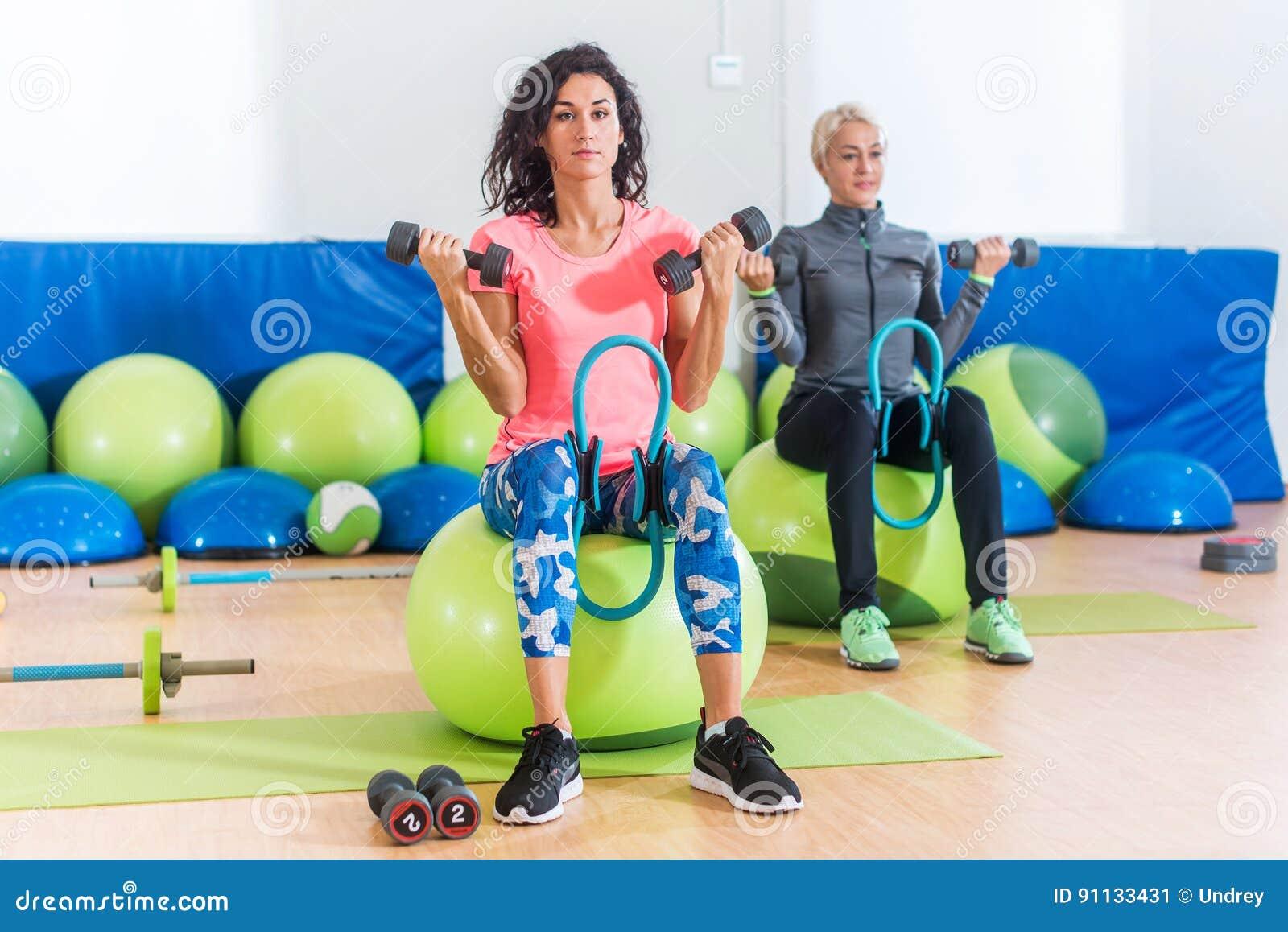 Slanka sportiga kvinnor som utbildar sammanträde på övningsbollar som rymmer hantlar och pressar den Pilates cirkeln mellan deras