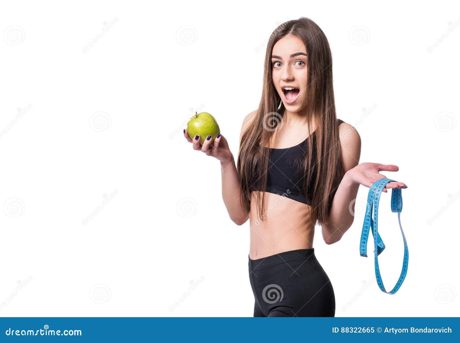Slanke en gezonde jonge die de maatregelenband en appel van de vrouwenholding op witte achtergrond wordt geïsoleerd Gewichtsverli