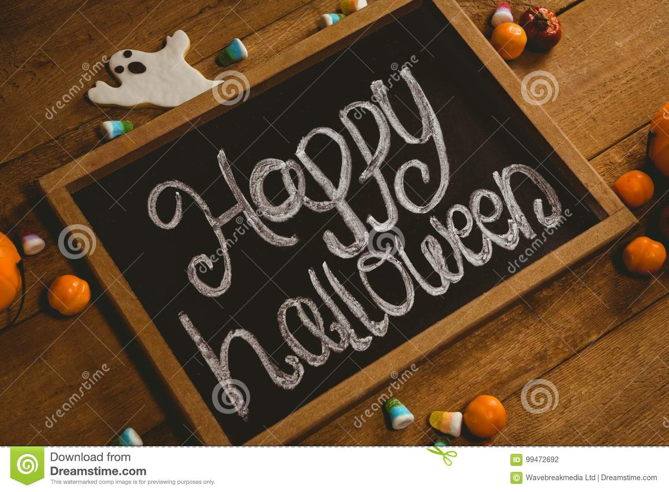 Slate with happy Halloween text by candies on wooden table