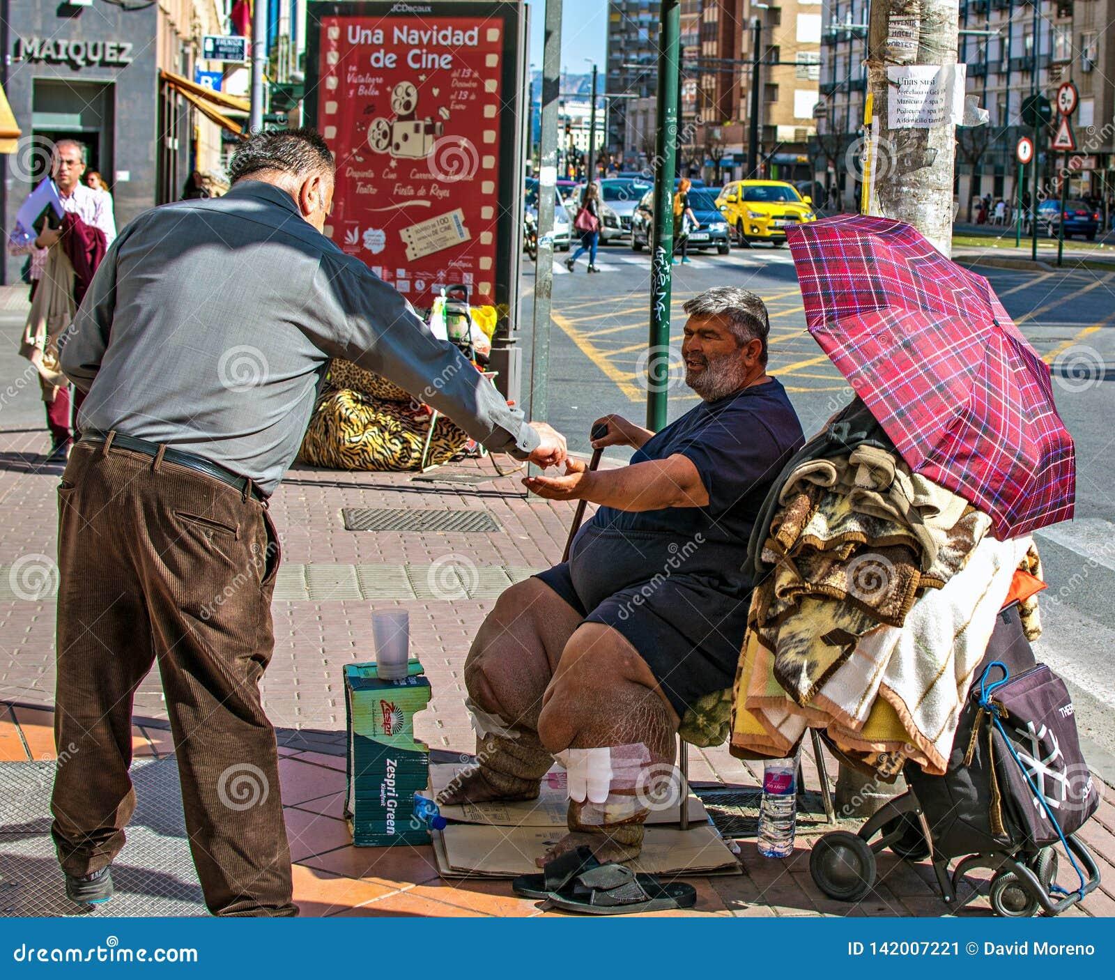 Slechte ongezonde mens die voor aalmoes in de straat van Murcia, Spanje bedelen De mens geeft geld aan armen