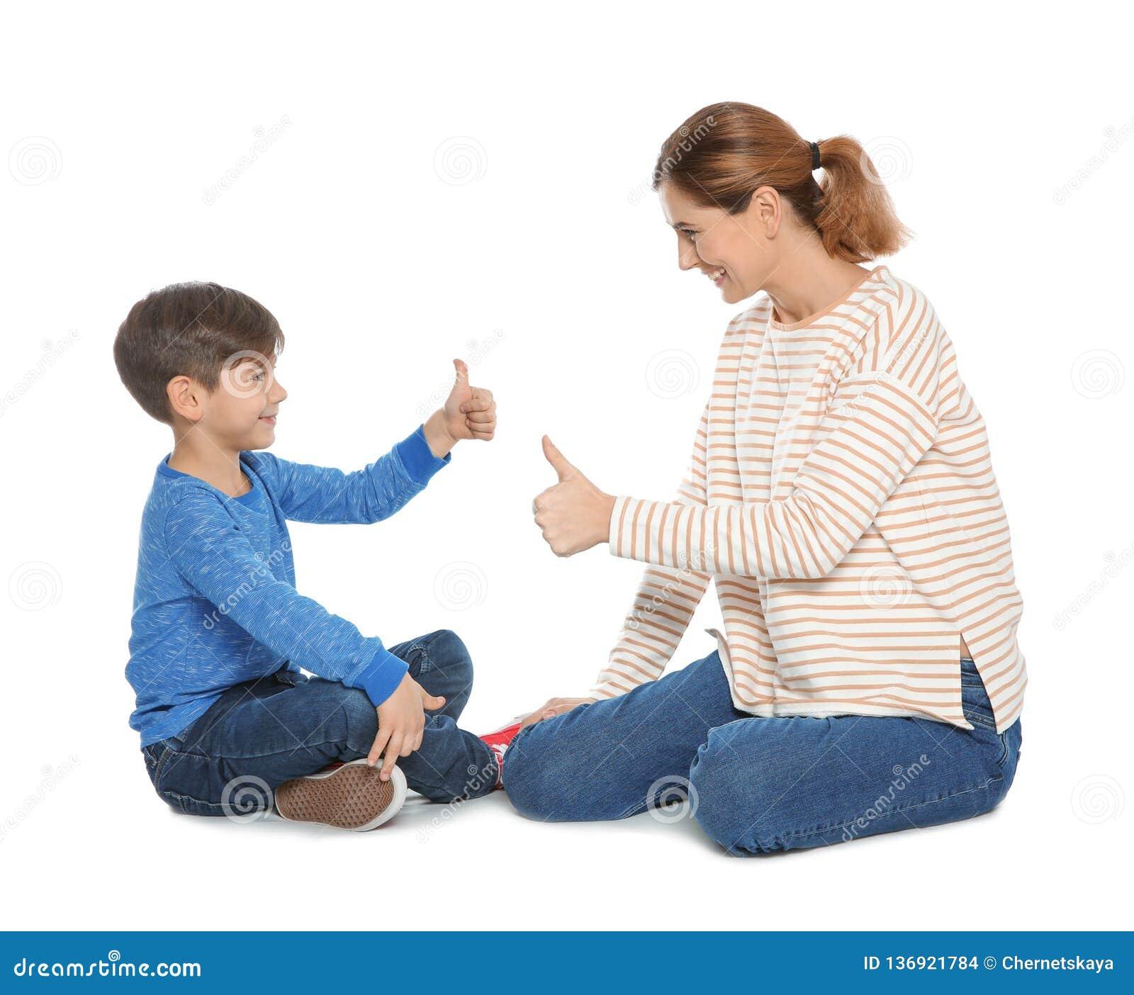 Slechthorende moeder en haar kind die met hulp van gebarentaal op wit spreken