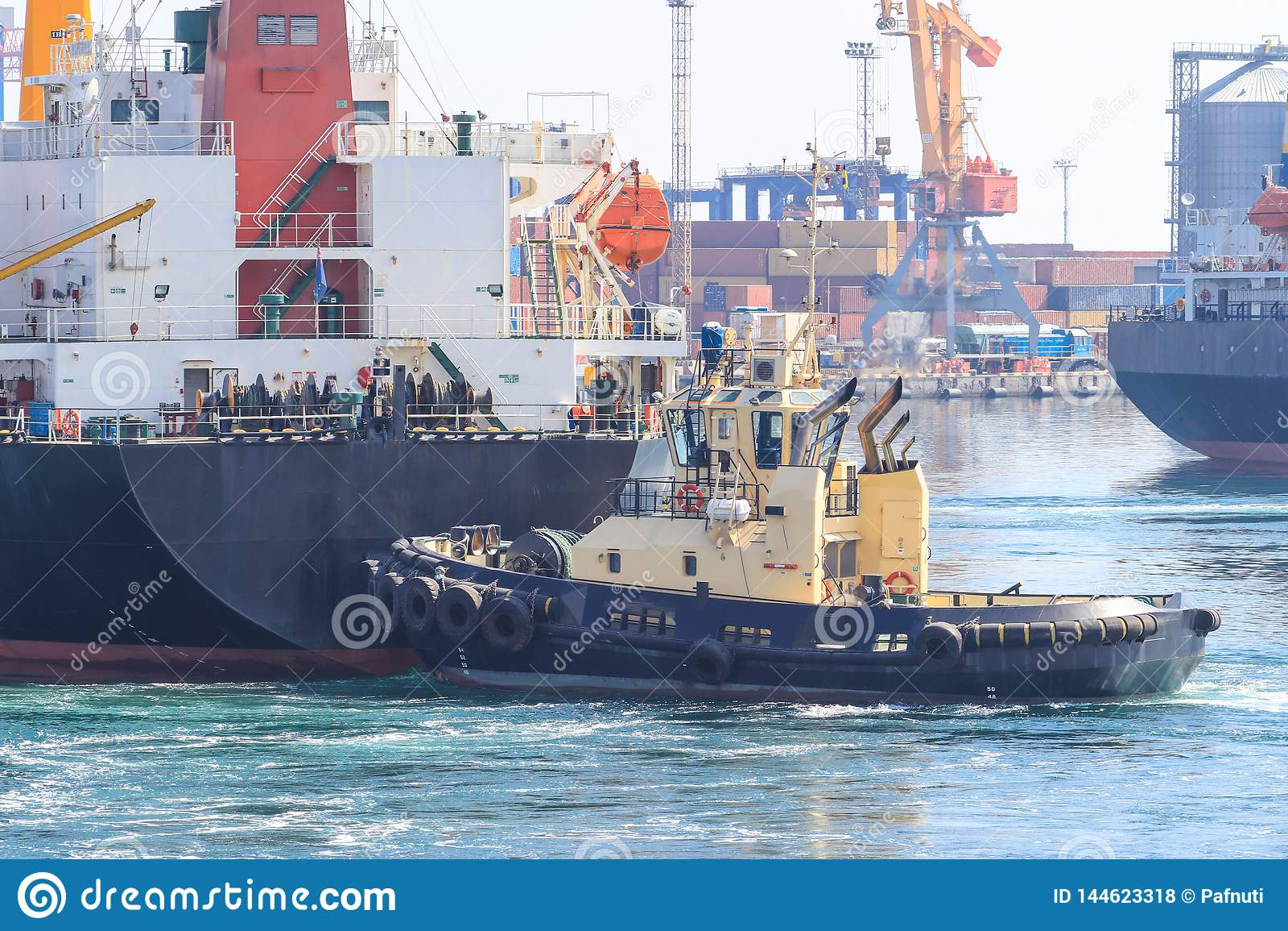 Sleepboot bij de boog die van vrachtschip, het schip bijstaan om in Zeehaven te manoeuvreren