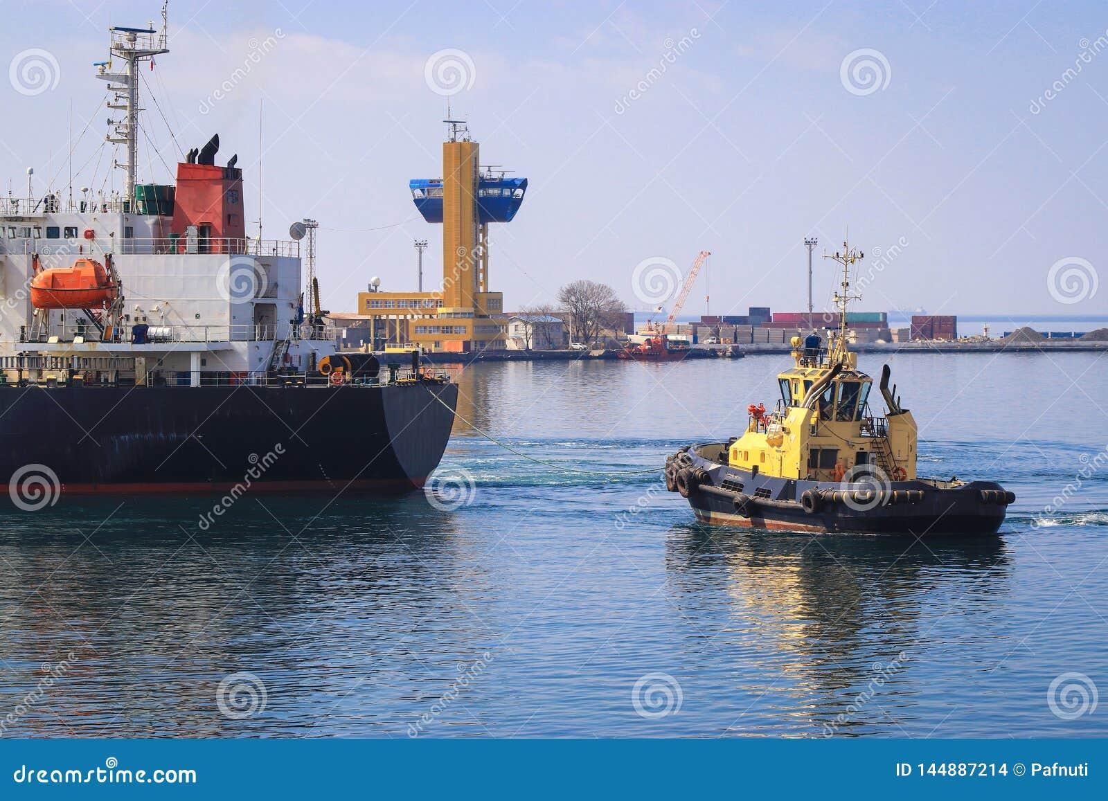Sleepboot bijwonend die Vrachtschip in de Haven van Odessa, de Oekraïne wordt gemanoeuvreerd
