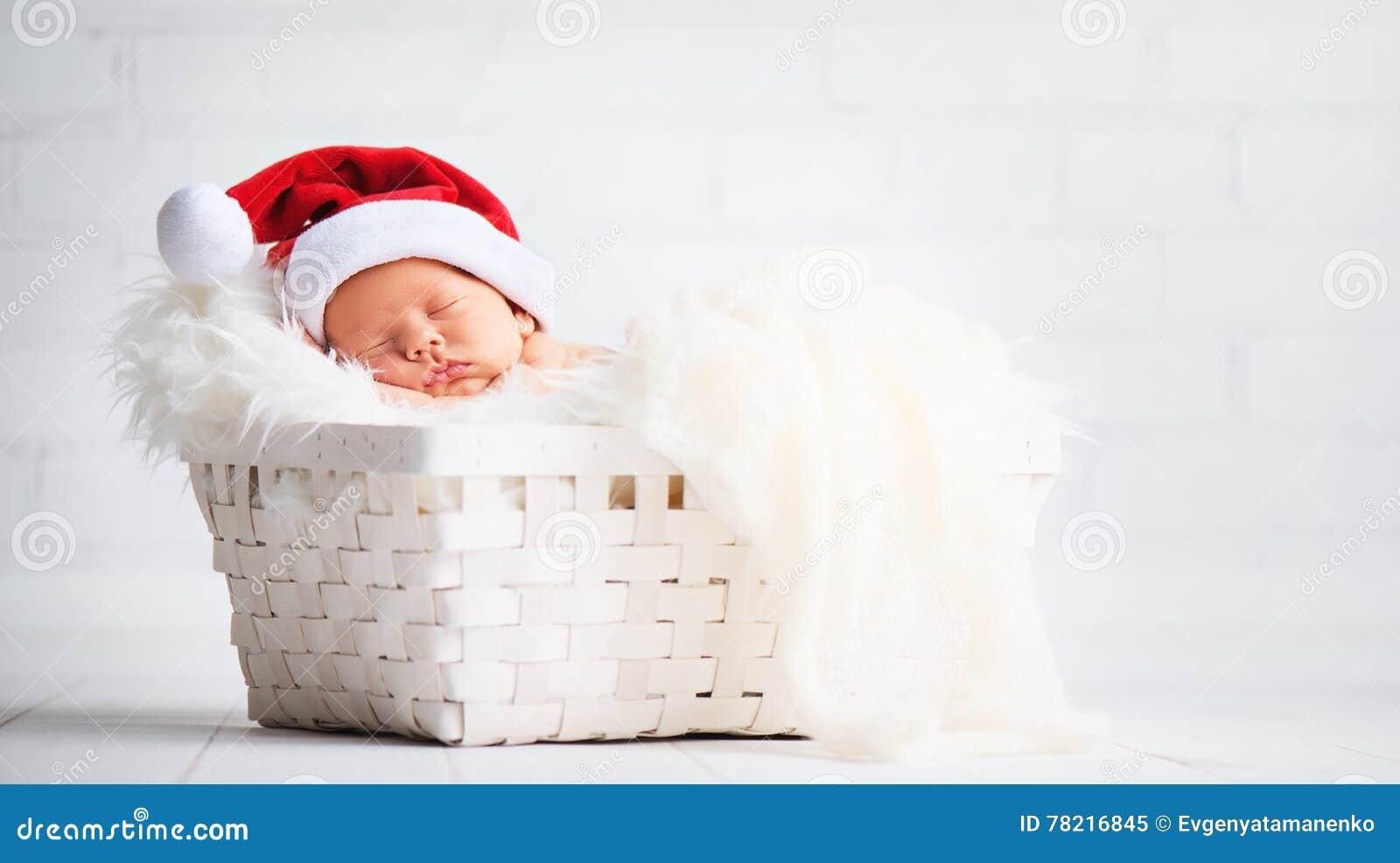 Sleeper newborn baby in Christmas Santa cap