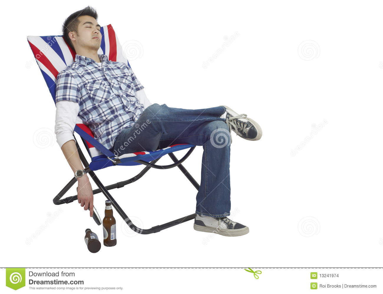 Young Asian man asleep in a chair with a remote in his hand and beers ...
