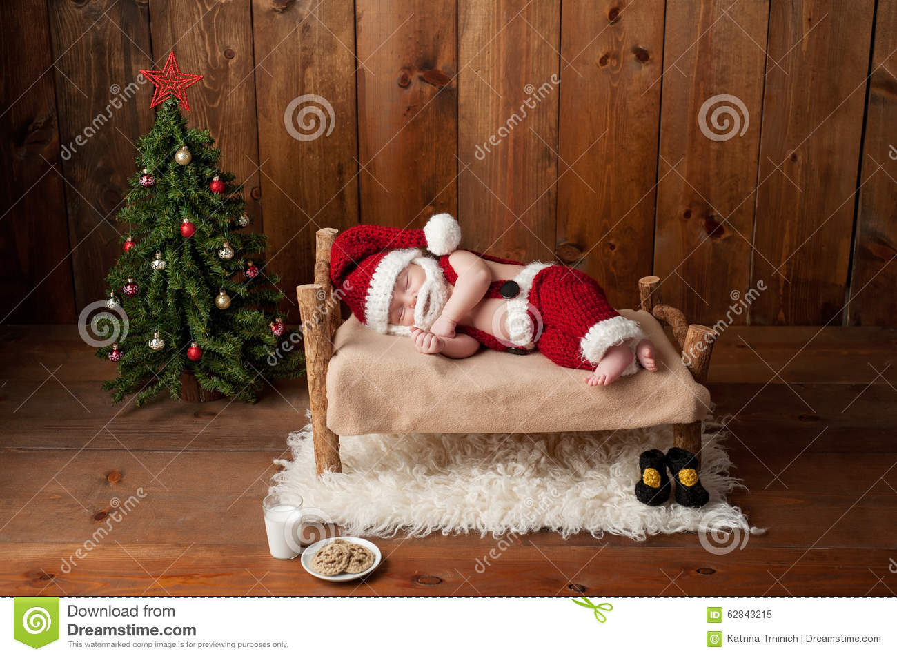 Two week old newborn baby boy wearing a crocheted santa suit and sleeping on a tiny wooden bed shot in the studio with props including a christmas tree