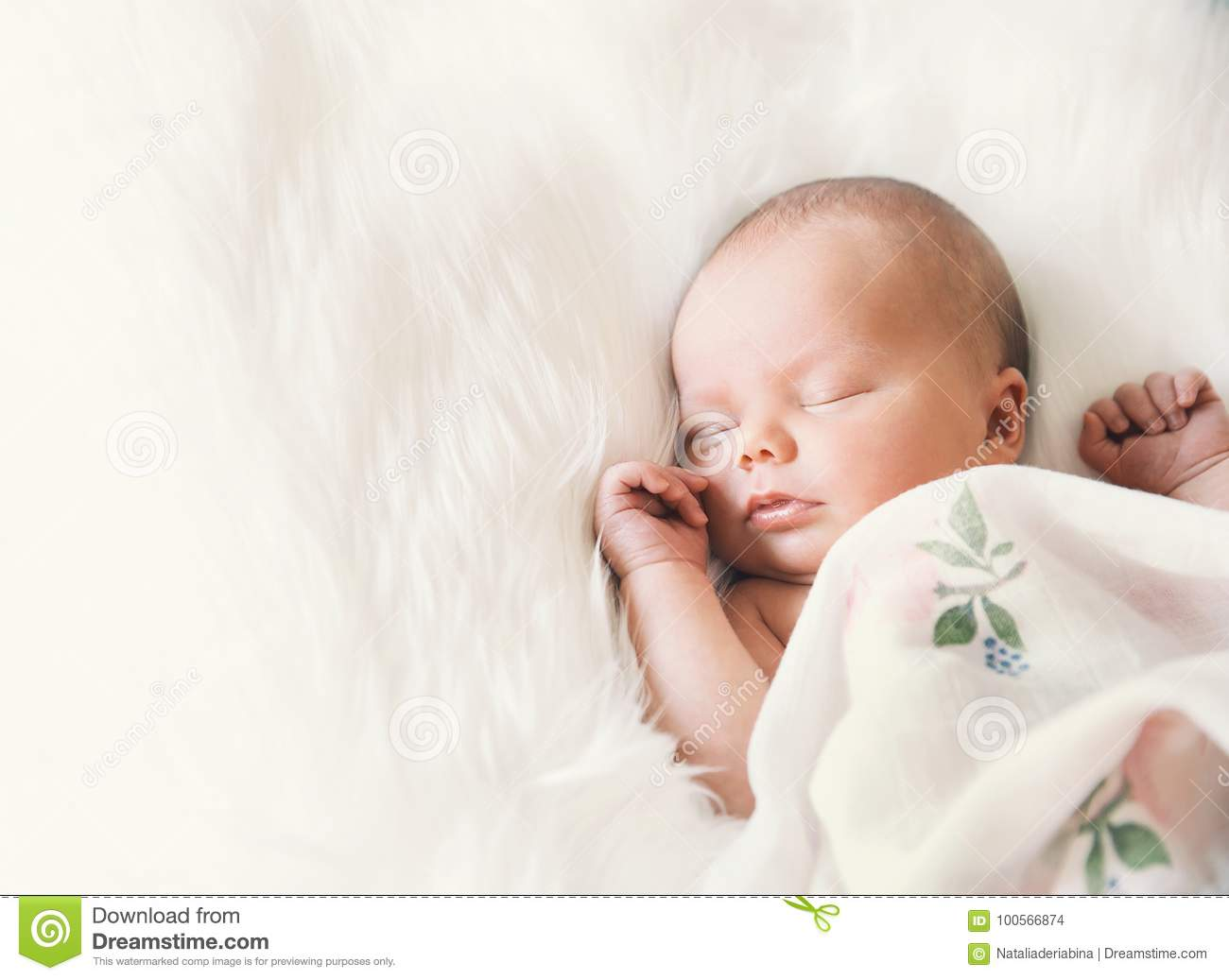 Sleeping Newborn Baby In A Wrap On White Blanket Stock Photo