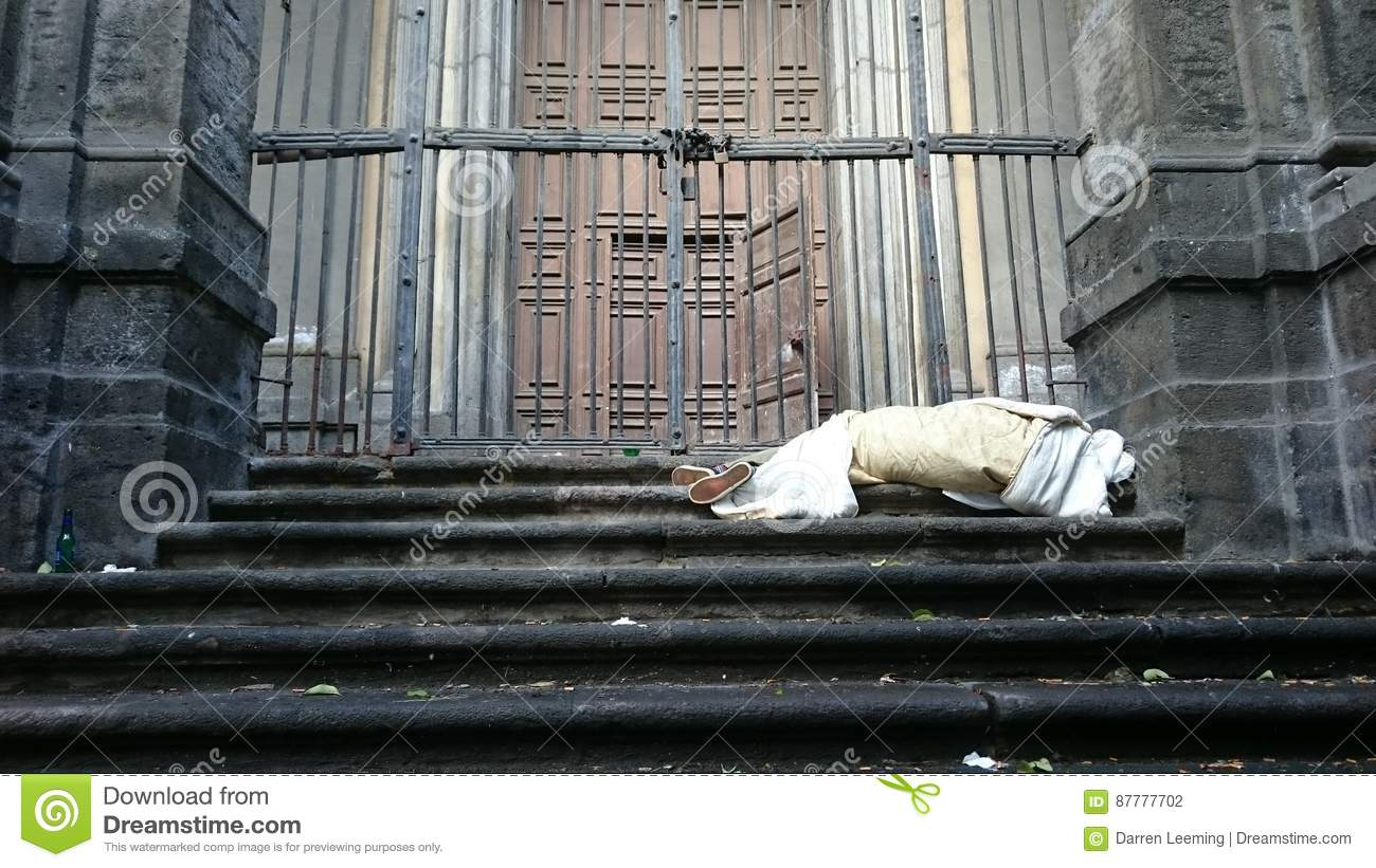 Sleeping Rough Homeless On The Stairs Of The Building In Front Of