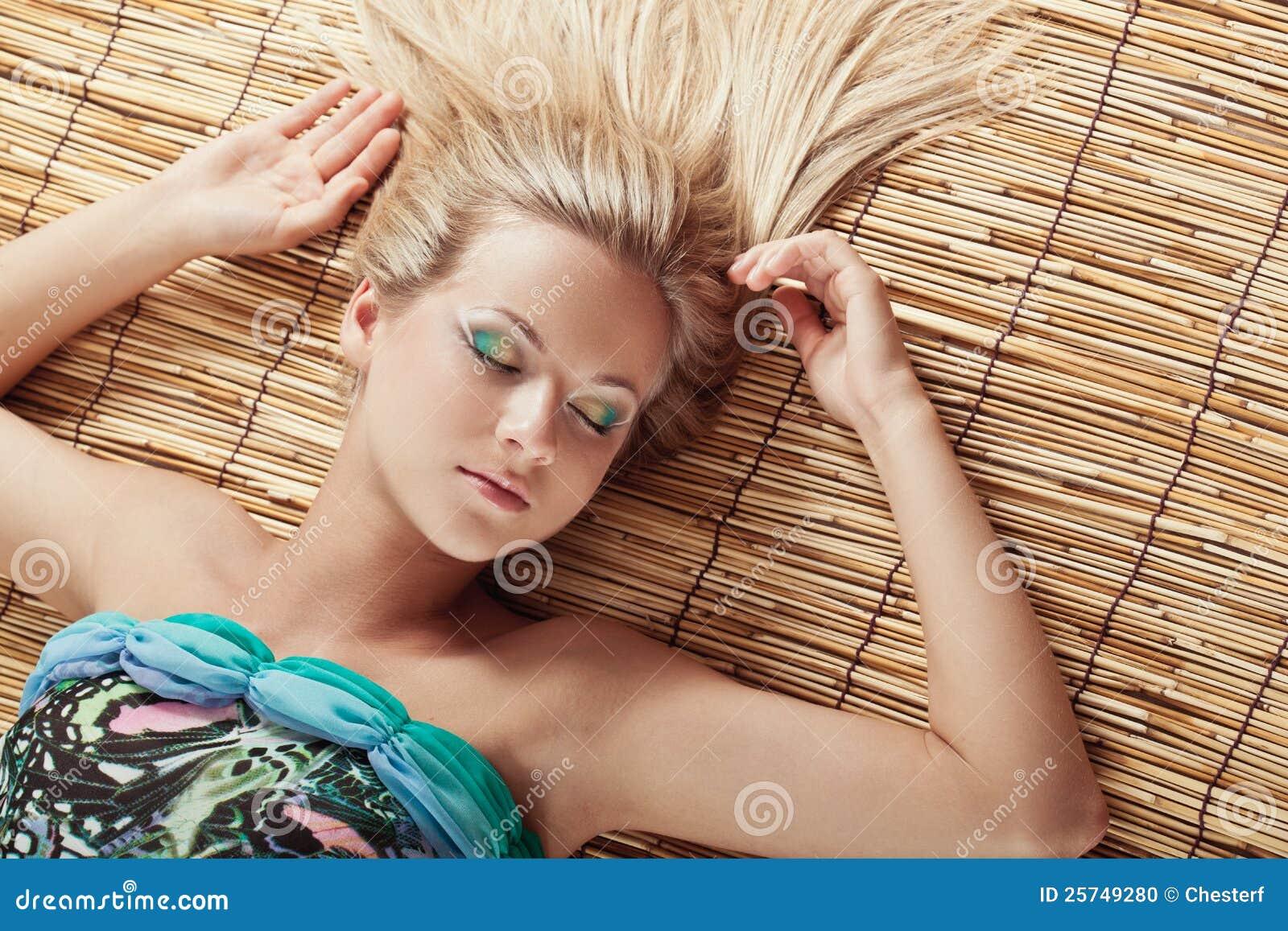 Sleeping woman laying on bamboo mat