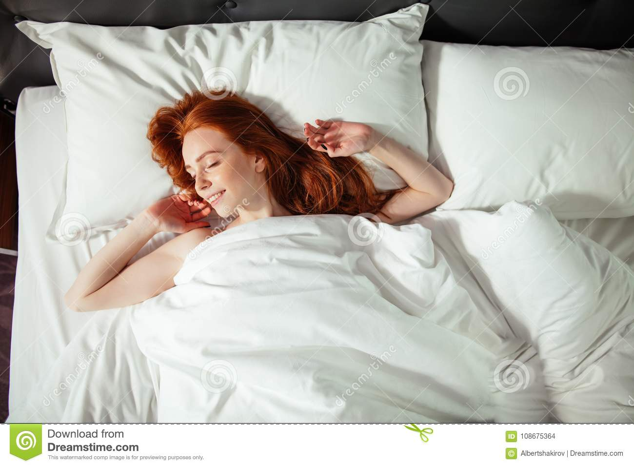 Sleeping young woman lies in bed with eyes closed. top view