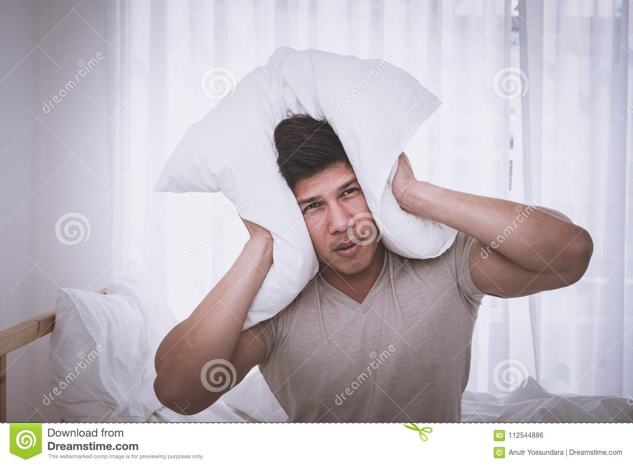 Sleepless male cover head fro noise and headache