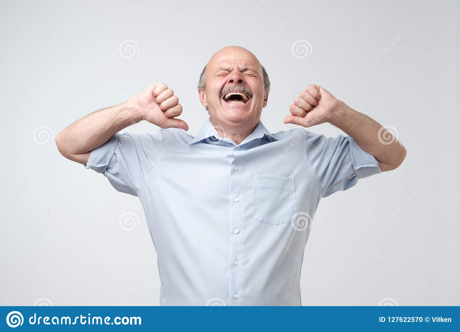 Sleepy mature bald man with mustache is yawning, because he is tired.