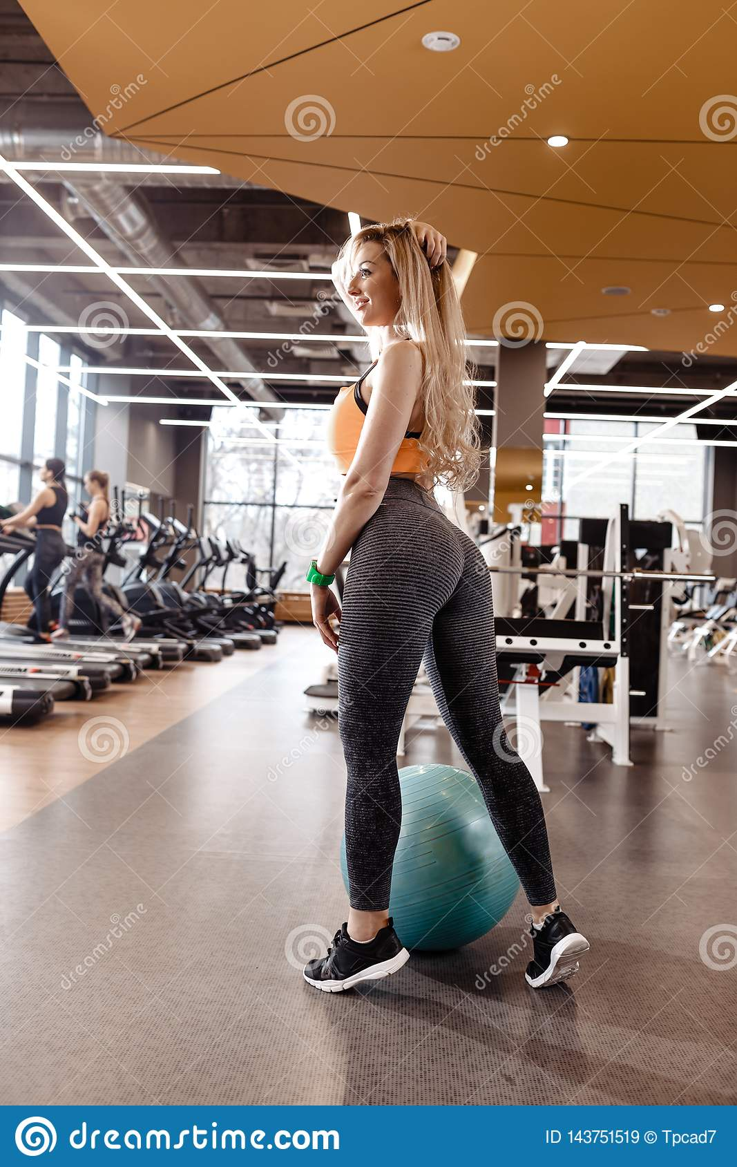 Slender blond girl with long hair dressed in a sportswear is posing next to the fitness ball in the modern gym with a