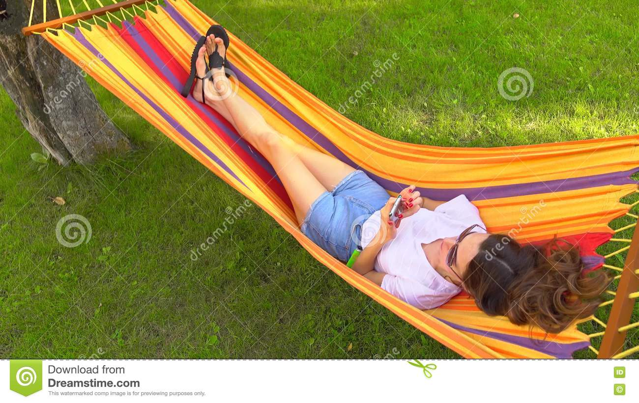 beautiful bright brunette girl hammock mobile ... - Slender Pretty Brunette Laying In Bright Hammock And Using Her