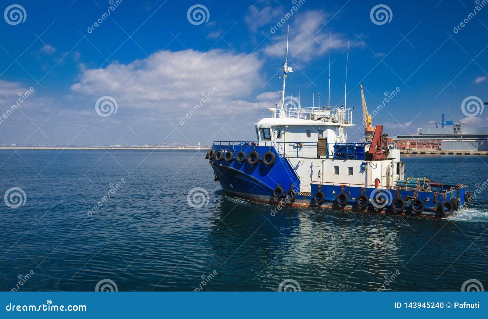 Slepend schip in de open zee, blauwe sleepboot die op overzees varen