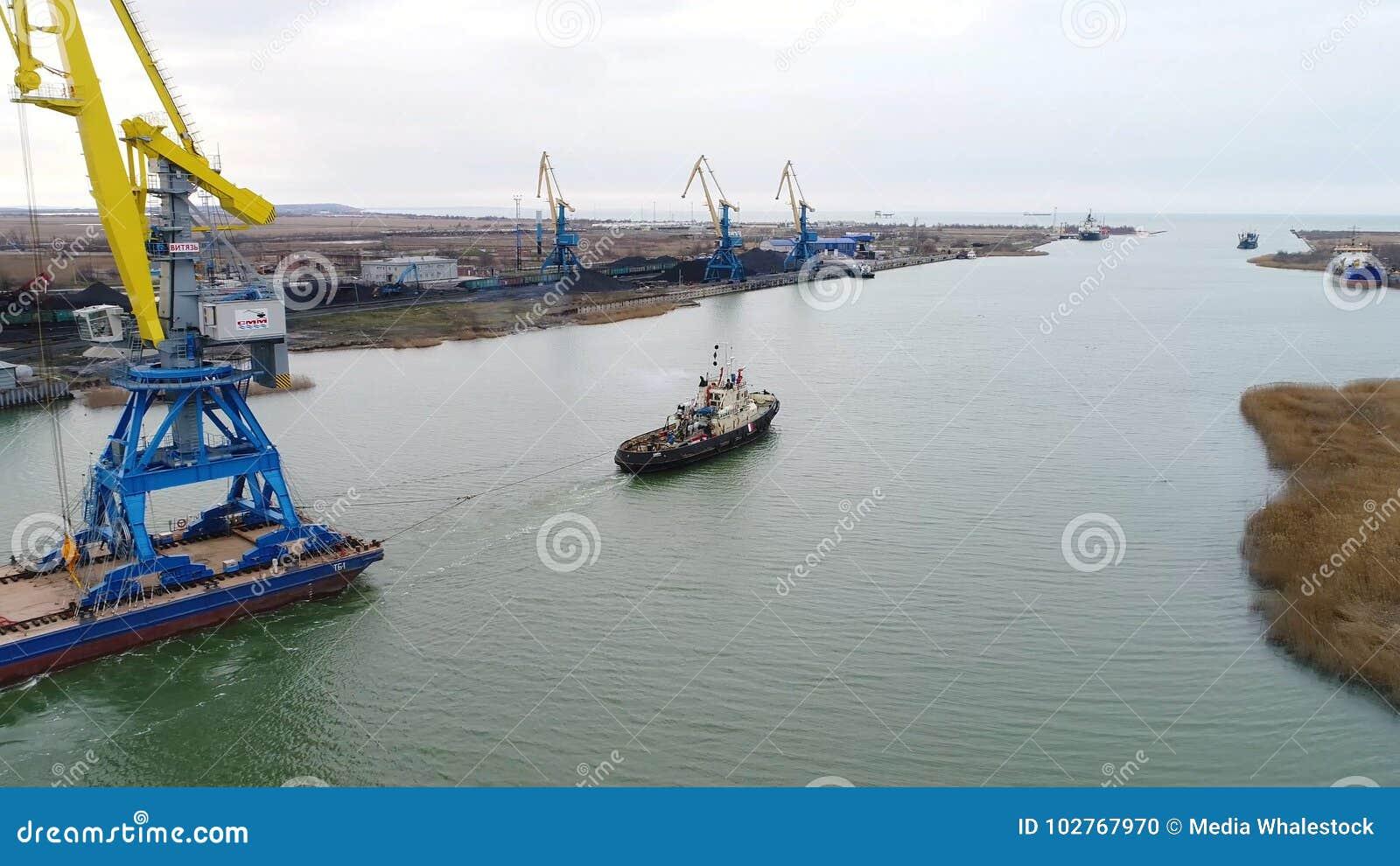 Slepende kranen voor containers Groot die containerschip door sleepboten wordt getrokken Top down luchtmening De vracht van de co