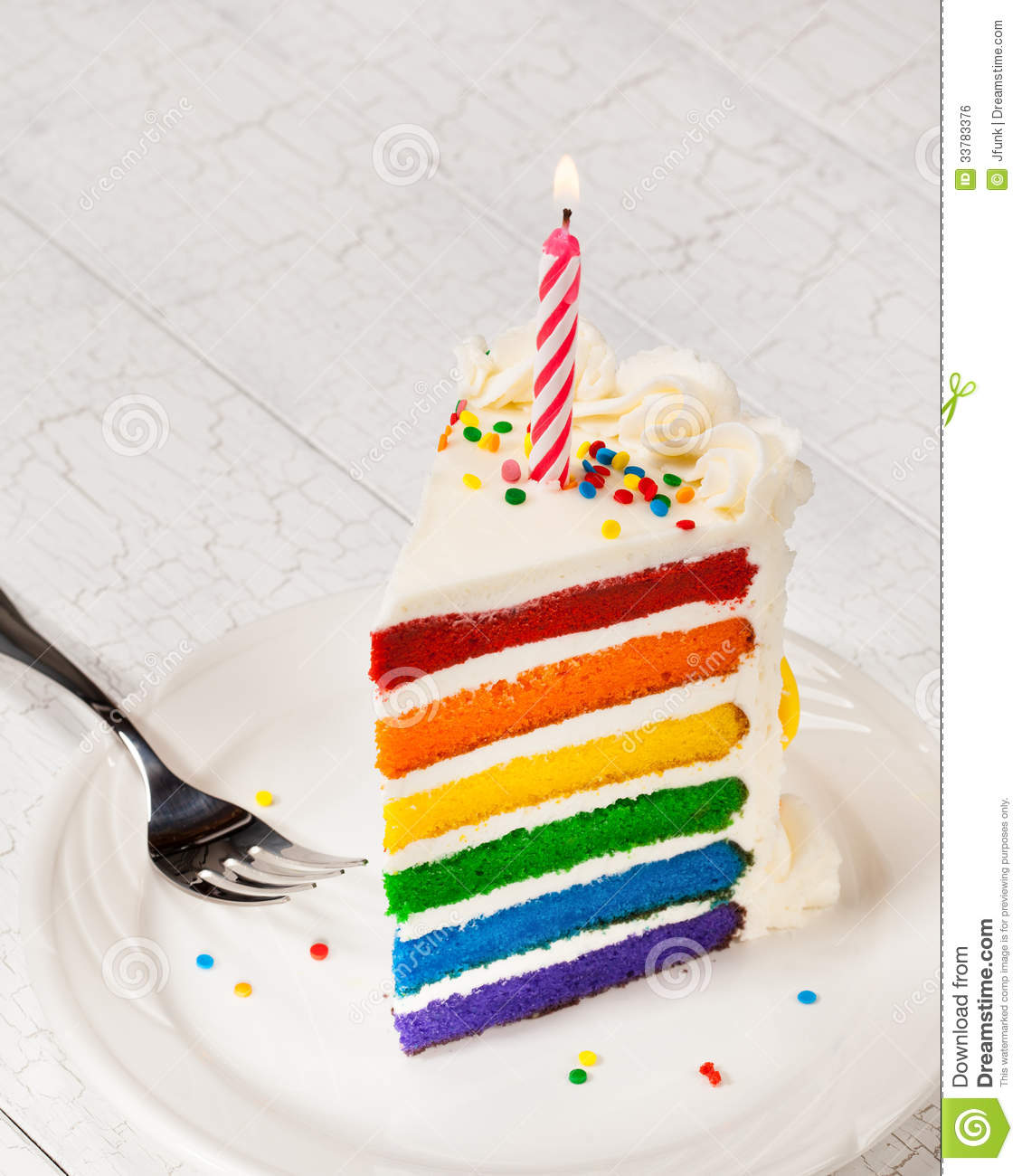 Slice Of Colourful Rainbow Layered Birthday Cake Decorated With Sprinkles Buttercream Icing And Lit Candle Copy Space For Your Text