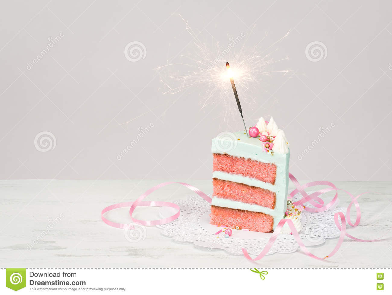 Slice Of Birthday Cake Over White Background With Pink Layers And Sparkler