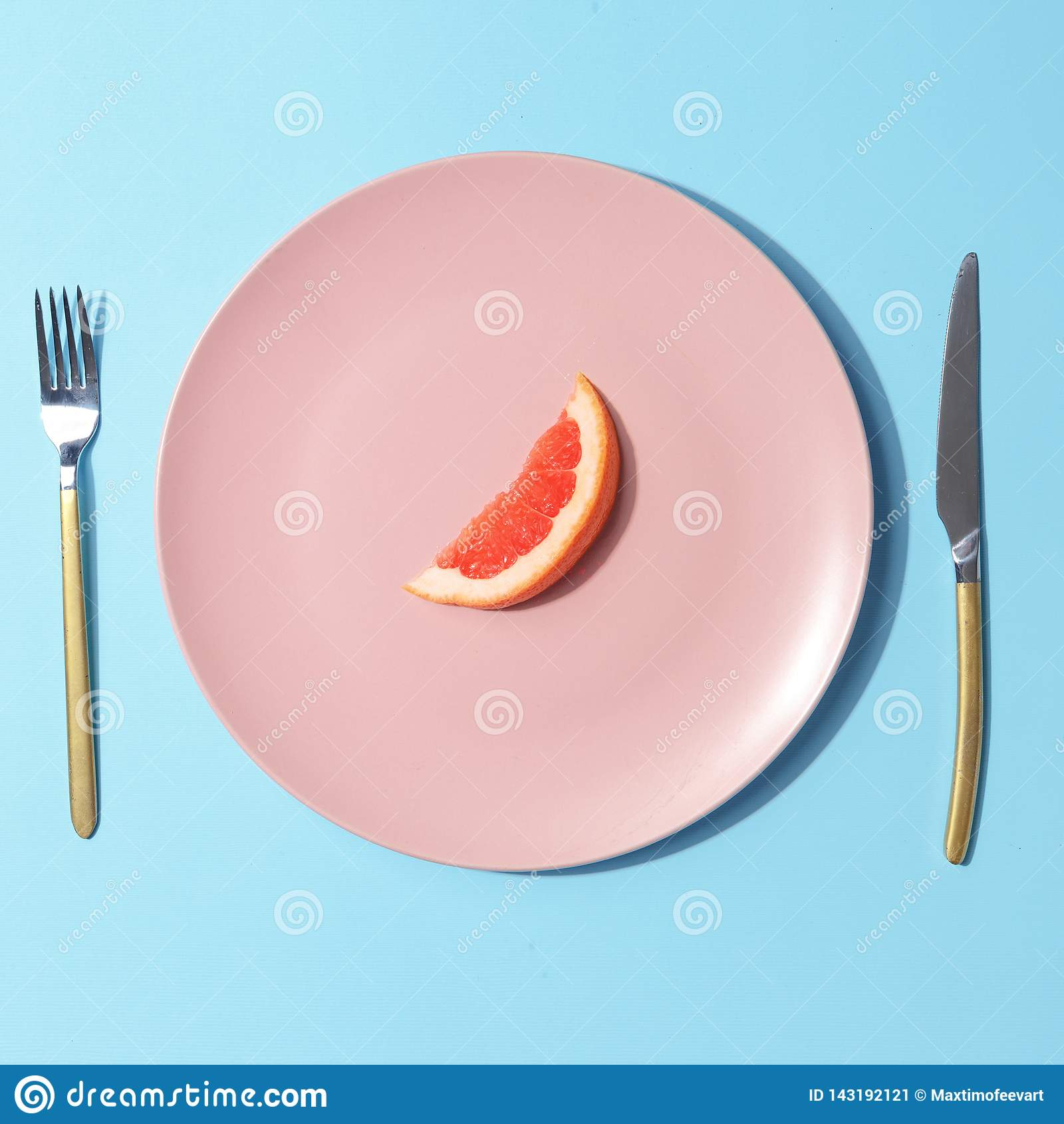 A slice of grapefruit on a pink plate. Minimalistic concept. Top view
