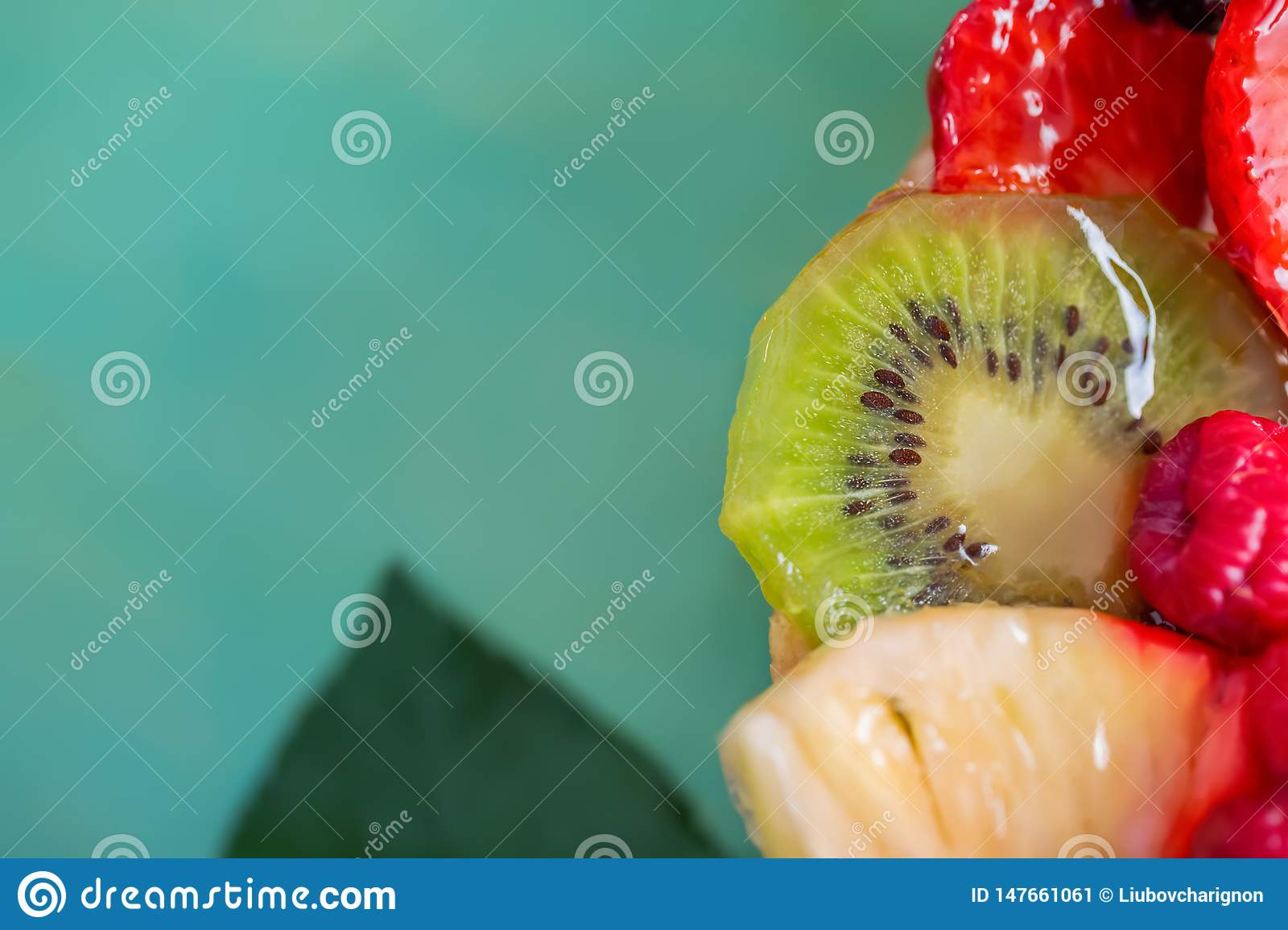 Slice kiwi and a variety of fresh fruits in sweet gelatin. Berries close-up in soft focus. Delicious dessert.