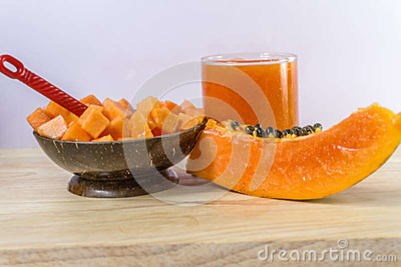 Slice of papaya isolated on the wooden table